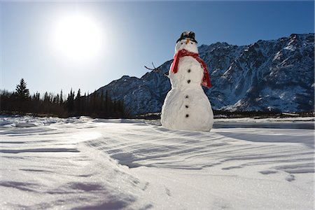 Snowman with a red scarf and black top hat sitting on the frozen Nenana River with the Alaska Range foothills in the background, Southcentral Alaska, Winter Stock Photo - Rights-Managed, Code: 854-03646513