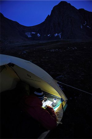 Woman in a tent at dusk consults a GPS and map while camping at Rabbit Lake, Chugach State Park, Southcentral Alaska, Autumn Stock Photo - Rights-Managed, Code: 854-03739552