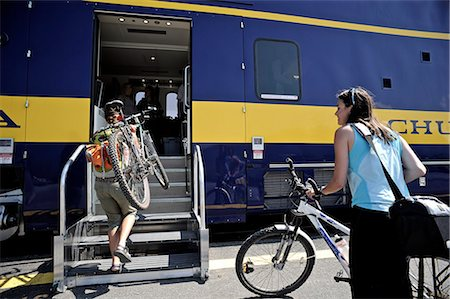 Two female bicyclists board the Alaska Railroad's Chugach Explorer in Portage for a whistle stop trip to Spencer Glacier, Southcentral Alaska, Summer Stock Photo - Rights-Managed, Code: 854-03739659