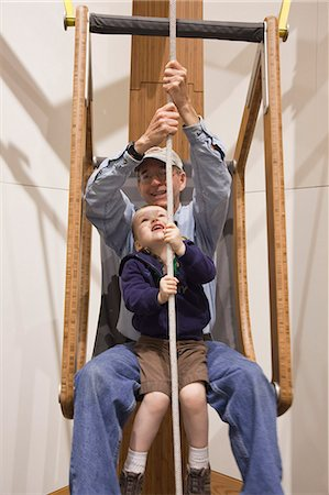 Grandfather and toddler grandson sit together and lift themselves with a rope and pulley system at the Imaginarium, Anchorage Museum at the Rasmuson Center, Southcentral Alaska, Summer Stock Photo - Rights-Managed, Code: 854-03740016