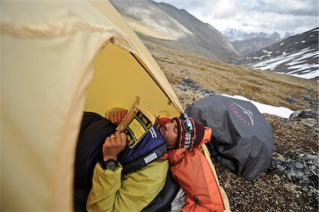 Backpacker reads a book inside a tent and waits out inclement weather at an alpine camp below Mt. Chamberln, Brooks Range, ANWR, Arctic Alaska, Summer Stock Photo - Rights-Managed, Code: 854-03740058