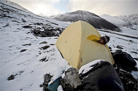 Backpacker sits inside a tent and waits out inclement weather at an alpine camp below Mt. Chamberln, Brooks Range, ANWR, Arctic Alaska, Summer Stock Photo - Rights-Managed, Code: 854-03740060