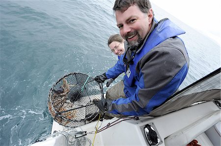 Couple celebrates catching a bunch of six-inch shrimp in Prince William Sound off Pt. Pigot, about 10 miles west of Whittier, Southcentral Alaska, Spring Stock Photo - Rights-Managed, Code: 854-03740334