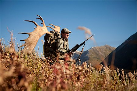Male moose hunter stops to enjoy the view as he hikes out of hunt area with trophy moose antler on his pack, Bird Creek drainage area, Chugach Mountains, Chugach National Forest, Southcentral Alaska, Autumn Stock Photo - Rights-Managed, Code: 854-03845062