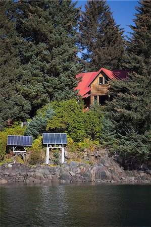 solar panel usa - Scenic view of a log home powered by solar panels in Anton Larsen Bay, Kodiak Island, Southwest Alaska, Summer Stock Photo - Rights-Managed, Code: 854-03845244