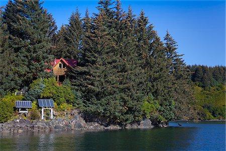 solar panel usa - Scenic view of a log home powered by solar panels in Anton Larsen Bay, Kodiak Island, Southwest Alaska, Summer Stock Photo - Rights-Managed, Code: 854-03845243
