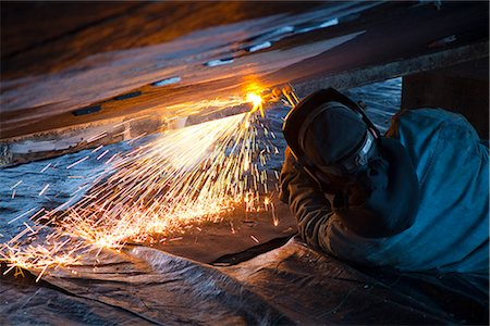 professional (pertains to traditional blue collar careers) - Worker cuts metal fittings off a boat hull using an oxy-acetylene cutting torch, Kodiak Boatyard, Saint Herman Harbor, Kodiak, Near Island, Southwest Alaska, Autumn Stock Photo - Rights-Managed, Code: 854-03845278