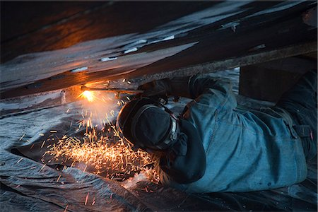professional (pertains to traditional blue collar careers) - Worker cuts metal fittings off a boat hull using an oxy-acetylene cutting torch, Kodiak Boatyard, Saint Herman Harbor, Kodiak, Near Island, Southwest Alaska, Autumn Stock Photo - Rights-Managed, Code: 854-03845280