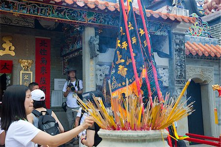 Worshipper offering incense at Pak Tai Temple during the Bun festival, Cheung Chau, Hong Kong Stock Photo - Rights-Managed, Code: 855-06313309