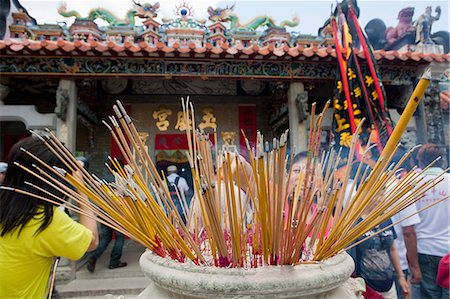 Worshipper offering incense at Pak Tai Temple during the Bun festival, Cheung Chau, Hong Kong Stock Photo - Rights-Managed, Code: 855-06313352