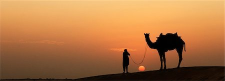 rajasthan camel - Silhouette of a man standing with a camel, Jaisalmer, Rajasthan, India Stock Photo - Rights-Managed, Code: 857-03192631