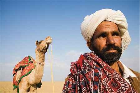 rajasthan camel - Close-up of a man with a camel in the background, Thar Desert, Jaisalmer, Rajasthan, India Stock Photo - Rights-Managed, Code: 857-03192653