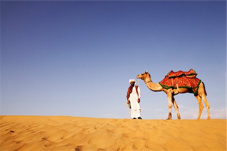 rajasthan camel - Man standing with a camel in a desert, Thar Desert, Jaisalmer, Rajasthan, India Stock Photo - Rights-Managed, Code: 857-03553609