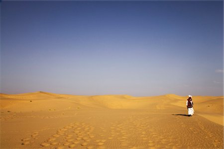 Man standing in a desert, Thar Desert, Jaisalmer, Rajasthan, India Stock Photo - Rights-Managed, Code: 857-03553611