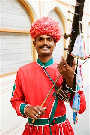 Mid adult man playing sarangi in a palace, City Palace, Jaipur, Rajasthan, India Stock Photo - Rights-Managed, Code: 857-03553621
