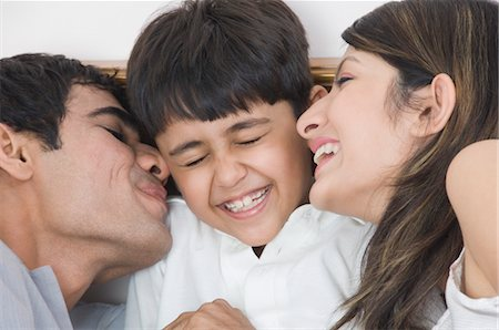 preteen kissing - Couple smiling with their son Stock Photo - Rights-Managed, Code: 857-03553779