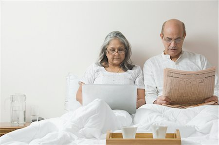 Man reading a newspaper with a woman using a laptop on the bed Stock Photo - Rights-Managed, Code: 857-03553875