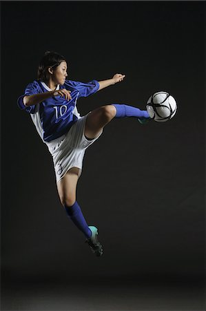 female playing soccer - Japanese Woman Reaching Up To Hit Ball Stock Photo - Rights-Managed, Code: 858-06118963