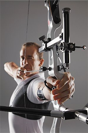 Male Archer Aiming With Bow And Arrow Stock Photo - Rights-Managed, Code: 858-06121545