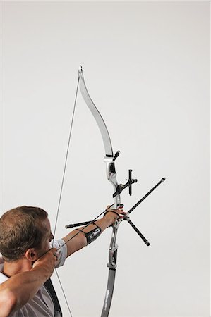 Man Aiming With Bow And Arrow Stock Photo - Rights-Managed, Code: 858-06121556