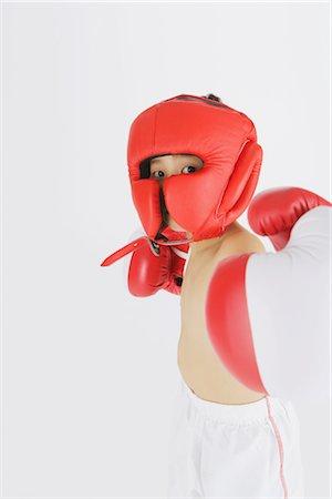 Kick boxer punching and looking at camera Stock Photo - Rights-Managed, Code: 858-03050028