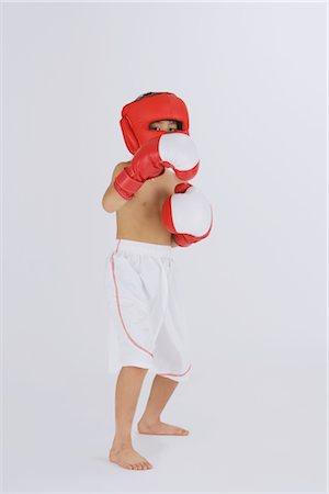 Kick boxer punching and looking at camera Stock Photo - Rights-Managed, Code: 858-03050029
