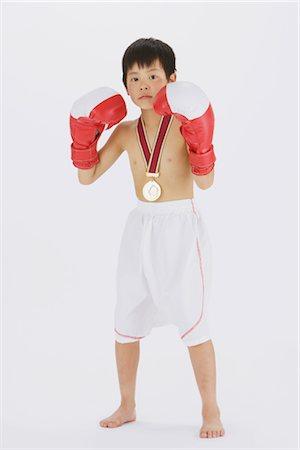 Kick boxer punching and looking at camera Stock Photo - Rights-Managed, Code: 858-03050030