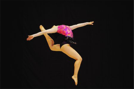 Gymnast jumping in mid-air performing rhythmic gymnastics Stock Photo - Rights-Managed, Code: 858-03799627