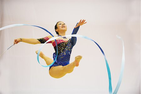 Young woman performing rhythmic gymnastics with ribbon Stock Photo - Rights-Managed, Code: 858-03799636