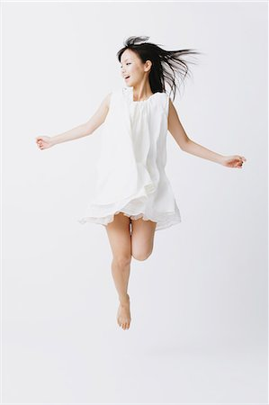 flying happy woman images - Asian woman in a white dress jumping Stock Photo - Rights-Managed, Code: 859-06404917