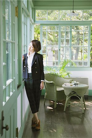 Japanese woman in a black jacket standing by the window Stock Photo - Rights-Managed, Code: 859-06404935