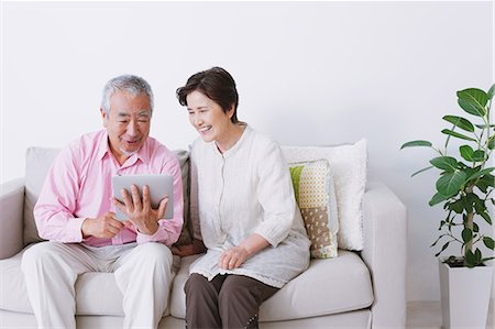 Senior adult couple sitting on a sofa with electronic tablet Stock Photo - Rights-Managed, Code: 859-06469760
