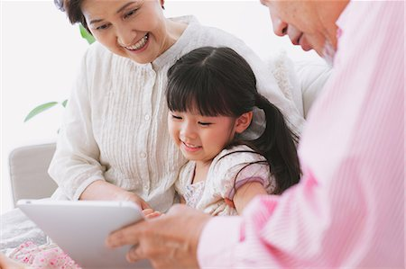 descriptive - Grandparents and granddaughter using electronic tablet on the sofa Stock Photo - Rights-Managed, Code: 859-06469762
