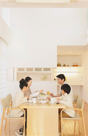 family table eating together - Family of four people eating at the dining table in the living room Stock Photo - Rights-Managed, Code: 859-06469838