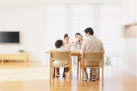 family table eating together - Family of four people eating at the dining table in the living room Stock Photo - Rights-Managed, Code: 859-06469839