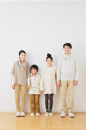 Family of four people holding hands while smiling at camera in front of a white wall Stock Photo - Rights-Managed, Code: 859-06469856