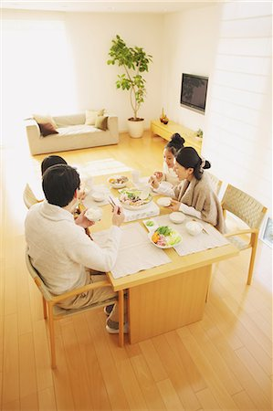 family table eating together - Family of four people eating at the dining table in the living room Stock Photo - Rights-Managed, Code: 859-06470174