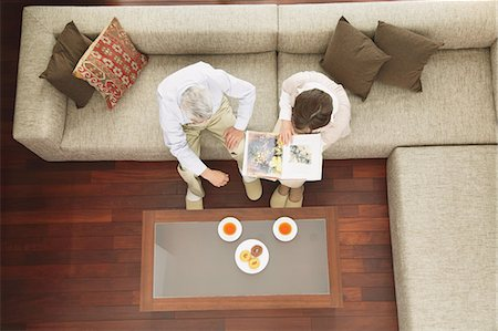 Above view of senior adult couple having tea and reading a book on the sofa Stock Photo - Rights-Managed, Code: 859-06470201
