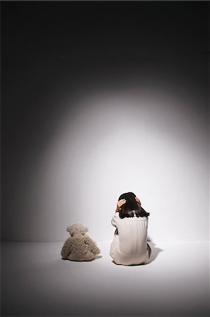 Girl in a white dress and teddy bear against a wall Stock Photo - Rights-Managed, Code: 859-06537705