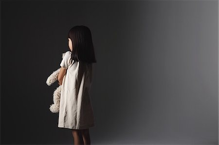 Girl in a white dress holding a teddy bear in front of a wall Stock Photo - Rights-Managed, Code: 859-06537714