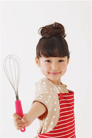 Young girl with apron smiling at camera Stock Photo - Rights-Managed, Code: 859-06537987