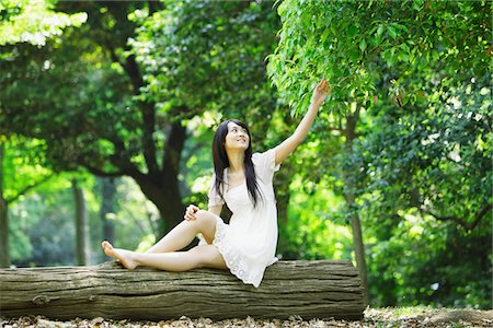 Young Woman Sitting on Tree Trunk Stock Photo - Rights-Managed, Code: 859-03782186