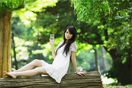 Young Woman Sitting  on Tree Trunk with Glass of Water Stock Photo - Rights-Managed, Code: 859-03782200