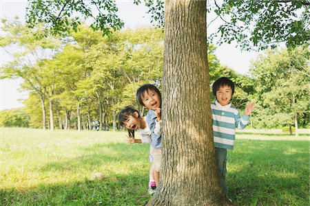 Children Hiding Behind Tree Trunk Stock Photo - Rights-Managed, Code: 859-03805798
