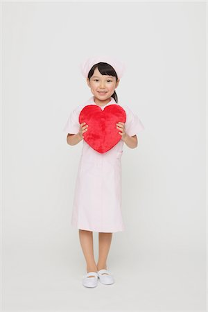 Girl Dressed As Nurse Holding Heart Stock Photo - Rights-Managed, Code: 859-03806086
