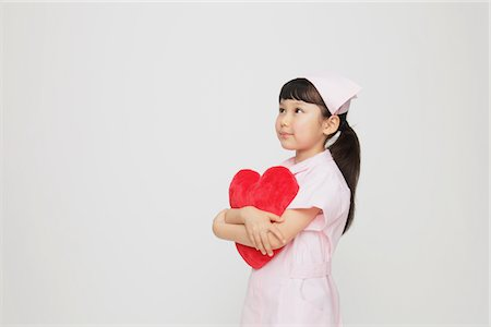 Girl Dressed As Nurse Holding Heart Stock Photo - Rights-Managed, Code: 859-03806097