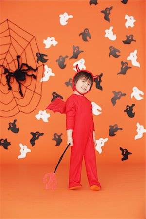 Boy Dressed Up As Devil against Orange Background Stock Photo - Rights-Managed, Code: 859-03806342