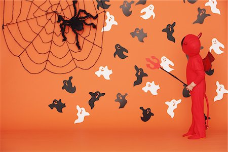 Boy Dressed Up As Devil against Orange Background Stock Photo - Rights-Managed, Code: 859-03806343