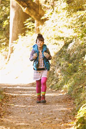 Young Woman Walking Alone On Path Through Forest Stock Photo - Rights-Managed, Code: 859-03839535