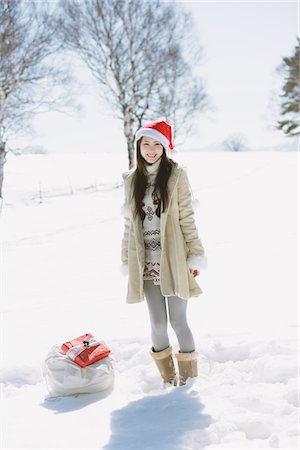 Teenage Girl Wearing Santa Hat Carrying Gifts Stock Photo - Rights-Managed, Code: 859-03860640